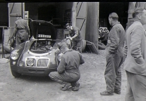 <h5>Le Mans 1955</h5><p>MGA twincam in the front and you can barely spot NOJ393's nose through the open door carrying nr. 26</p>